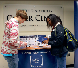 Jobs — Two students browse brochures outside the career center. Photo credit: Emily Becker