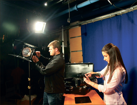 Experience — Atkins and Aube set up lighting and camera equipment for a broadcast. Photo credit: Ruth Bibby