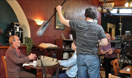 ON set — Professor James Walz helps position a boom mic on location at White Hart Café. Photo provided