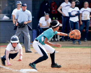 dive — a Lady Flames softball player slides head-first into first base against the Chanticleers. Photo credit: Katelyn Welch
