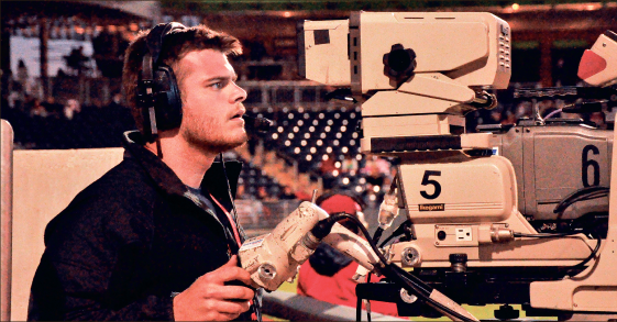 Captured — Matt Atkins works a camera during the live broadcast of a Liberty Flames baseball game. Photo credit: Greg Leasure