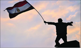 CIVIL UNREST — A protester holds up an Egyptian flag during demonstrations.