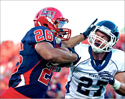 Shiver — Liberty running back Desmond Rice stiff arms Monmouth cornerback Andrew Sutton in a 45-15 rout. Photo credit: Ruth Bibby