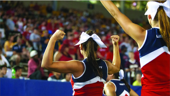 Commitment — Liberty cheerleaders display their team spirit during the football team's loss at Kent State, Aug. 29. Photo credit: Ruth Bibby