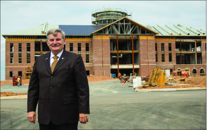 Construction — Dr. Ronnie Martin stands in front of the college that is nearing completion. Photo credit: Leah Stauffer