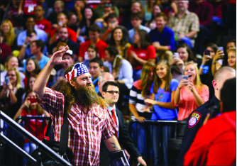 REALITY — Robertson responds to applause as he enters the Vines Center. Photo credit: Ruth Bibby