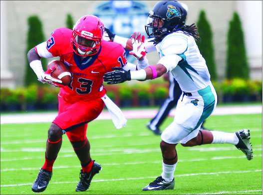 CREATING SPACE — Darrin Peterson (13) attempts to stiff-arm a defender in Liberty's loss to No. 3 Coastal Carolina. Photo credit: Courtney Russo