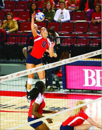 Spike — Lillie Happel (12) attempts to deliver a deciding blow in a 3-0 victory against Coastal Carolina.  Photo credit: Courtney Russo