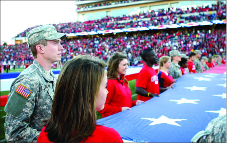 recognition —  Students and soldiers display a giant American flag covering most of the field during halftime of the Liberty vs. VMI football game. Photo credit: Ruth Bibby
