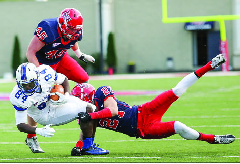 BIG EFFORT — Liberty's Jacob Hagen (27) dives to tackle Presbyterian's Tobi Antigha during the 35-14 Flames victory. Photo credit: Ruth Bibby