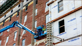 A worker lays bricks on Liberty's new dormitory tower. Photo credit: Courtney Russo