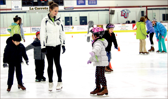 LEARNING — Children practice skating techniques with their instructor during lessons at the LaHaye Ice Center. Photo credit Abby Kourkounakis