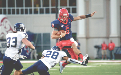 Rise Up —  Quarterback Josh Woodrum hurdles over a diving Monmouth defender. Photo credit: Ruth Bibby