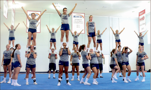 passion— Cheerleaders have practiced for hours each day to prepare to support the Flames football team. Photo credit: Leah Seavers