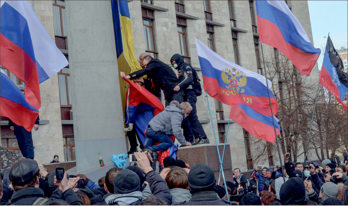 TRAVESTY — Pro-Russian protestors tear down Ukrainian flag and replace it with a Russian flag in front of the Donetsk Oblast Regional State Administration building. Google Images