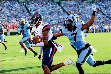 watch OUT — UNC cornerback Tim Scott reaches up to strip Liberty's Darrin Peterson in the first quarter. Photo credit: Courtney Russo