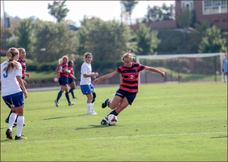 Lock Down — Maddie Boone (2) keeps the ball away from UNC-Asheville.  Photo credit: Leah Seavers