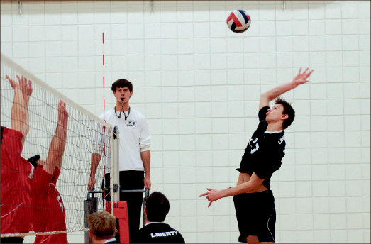 UNBEATEN — Middle blocker Sam Eisbrenner elevates for a spike as the Flames maintain their perfect season. Photo credit: Steven Abbott