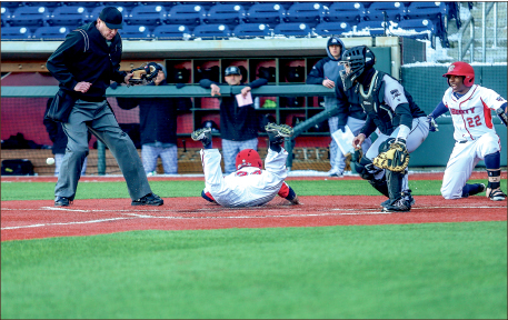 close call — Sophomore outfielder Will Shephard (34) dives for home plate just as the ball arives. Photo credit: Leah Seavers