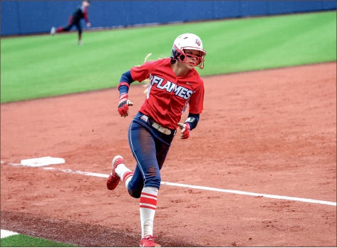 Coming Home — Center fielder Tori Zavodny rounds third against Coastal, scoring a run for the Lady Flames.  Photo credit: Leah Seavers