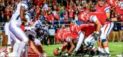 Trenches — Liberty Flames football team sets up for a goal-line push against Richmond in the 2014 Homecoming game. Photo credit: Leah Seavers