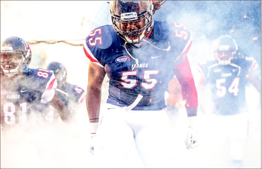 BIg Entrance — Flames defensive end Tolen Avery storms out of the tunnel before Liberty's home opener against Delaware State. Photo credit: Leah Seavers