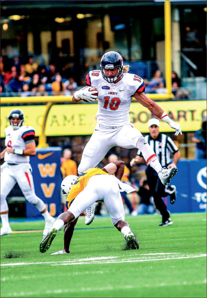 airborn — Junior tight end Will Johnson, transfer from West Virginia in his second year at Liberty,  catapults over a former teammate in Liberty's loss to the Mountaineers. Photo credit: Leah Seavers
