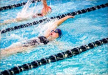 cruising — A Lady Flames swimmer competes in the backstroke during a spring 2015 event at Liberty's Aquatics Center. Photo credit: Leah Seavers