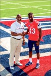 NEW START — Benjamin Alexander shakes hands with Head Football Coach Turner Gill. Photo credit: Joel Coleman