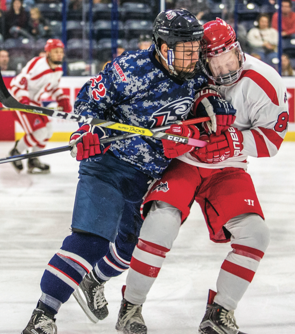 COLLISION — Forward Zak Hayes checked an opponent at the military appreciation hockey game Saturday, Nov. 5 against Stony Brook University. PC: Caroline Sellers / Liberty Champion