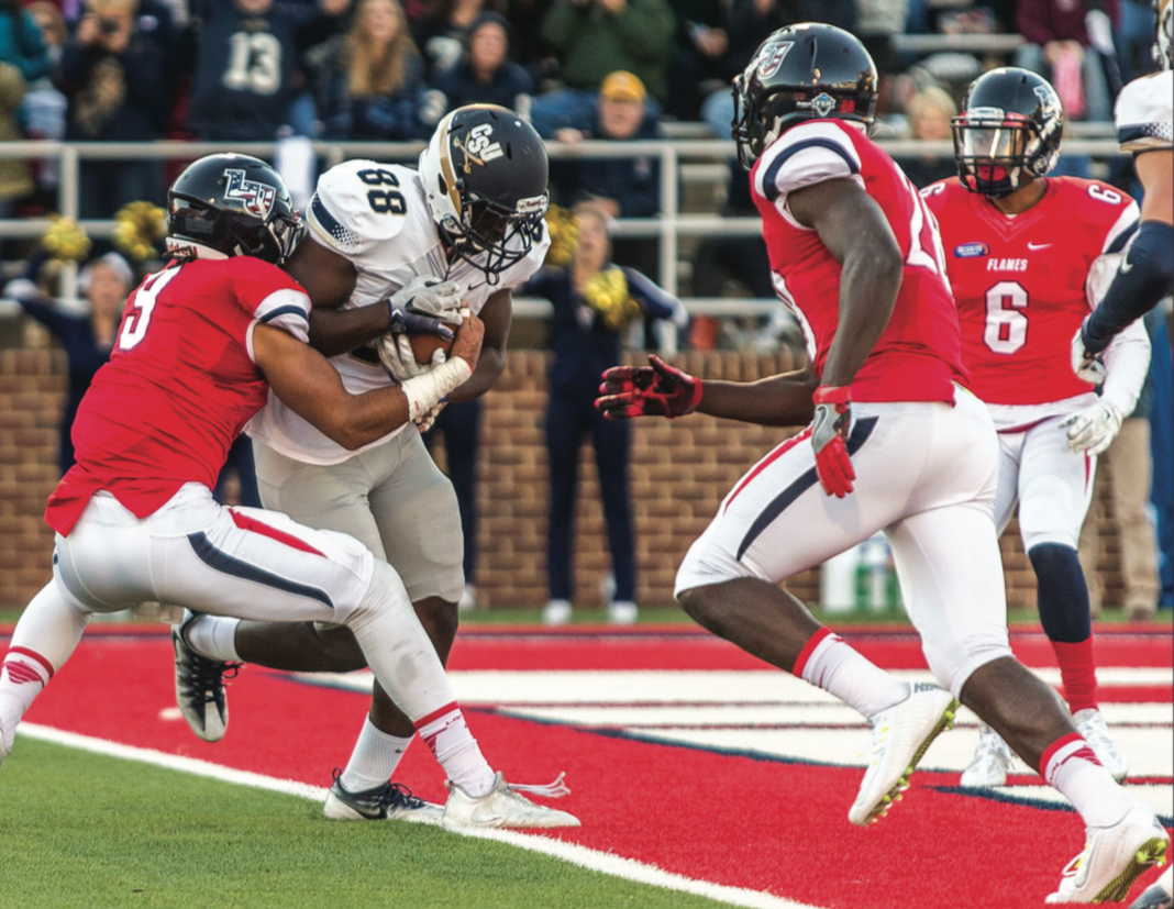 SCORE — Bucs tight end Travay Hatten plowed past Flames senior linebacker Nate Newman for the game's first touchdown. Photo credit: Michela Diddle