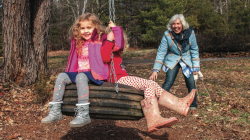 ENJOYING FAMILY — Debbie Perdew pushed two of her granddaughters on one of the tree farm's three tire swings. Photo credit: Amber Tiller