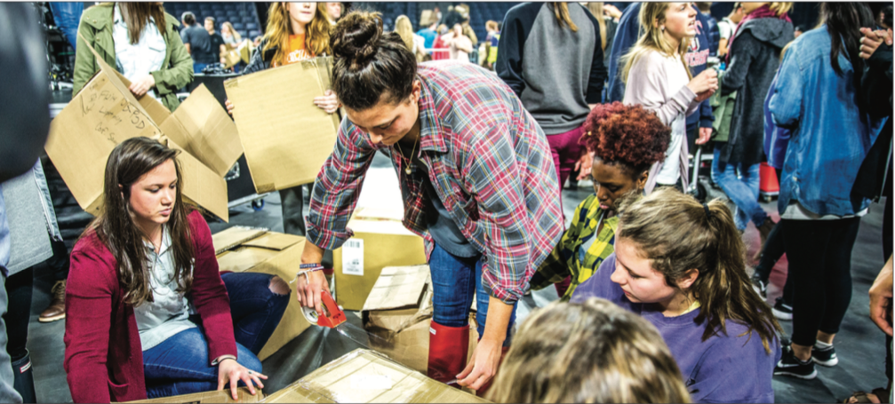WRAPPING IT UP — At Campus Community March 1, thousands of students packaged more 20,000 donated pairs of tennis shoes that will be sent to the Democratic Republic of the Congo. Photo Credit: Michela Diddle