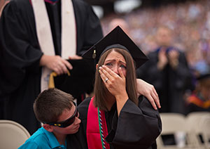 Malory Mallery reacts as her husband, Sgt. Mark Mallery, currently deployed in Afghanistan, shares his congratulations via video during the Commencement ceremony.