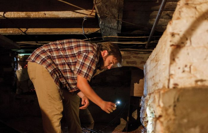 Ben Barker, a student in Liberty's first public history course, explores the foundation of Mead's Tavern, an 18th century building in Bedford County, Va., that the university recently purchased and plans to restore.