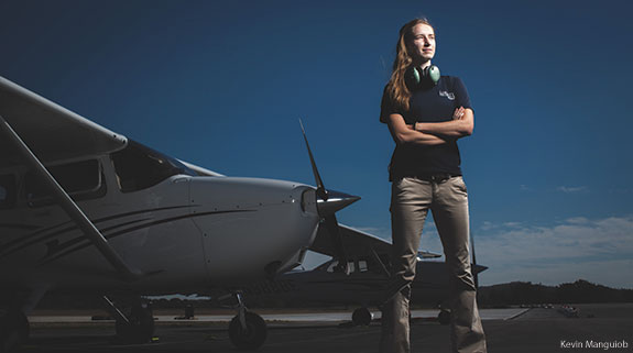 A Liberty University School of Aeronautics student poses in front of some of the school's planes.