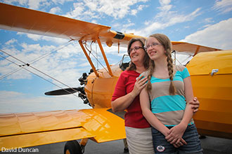 Visiting female pilots pose in front of a vintage plane at 2013 Women Can Fly.