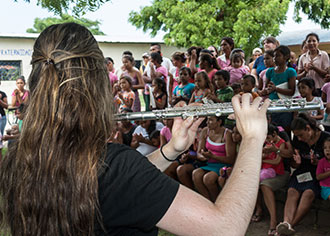 A Liberty University student plays flute for villagers in Nicaragua.