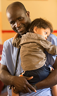 LUCOM student-doctor embraces a Guatemala child.
