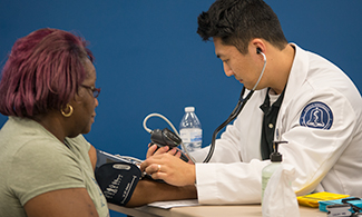 LUCOM student-doctor checks vitals of Danville outreach patient.