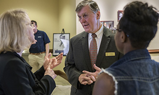 Gary L. Patton, Ph.D., Assistant Dean for Admissions, greets visitors during LUCOM Open House on Saturday, Oct. 1, 2016.