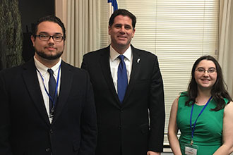 Ambassador Ron Dermer welcomes two Liberty University students to his office.