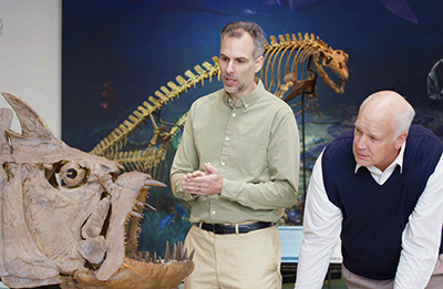 Dr. Marcus Ross (left) films a scene at Discovery Park of America (Tenn.) with host Dr. Del Tackett. The two are examining a skeleton of the extinct fish xiphactinus.