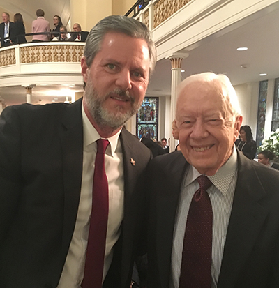 Liberty University President Jerry Falwell stands with former U.S. President Jimmy Carter after a private prayer service before Donald Trump swore in as president.