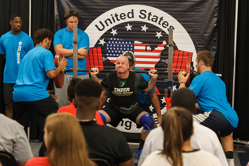 Liberty University Senior Vice President of Auxiliary Services Lee Beaumont raises the bar in the squat competition. (Photo by Joel Coleman)