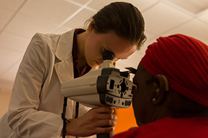LUCOM student-doctor examines eye of patient.