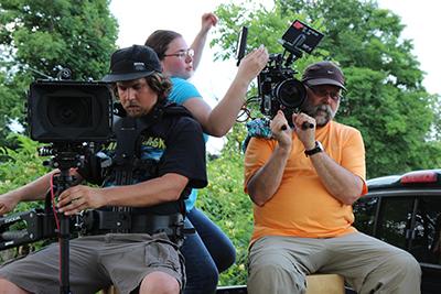 Liberty cinematic arts graduates Ian Miller (left) and Marissa Scalzo work alongside 'Texas Rein' director of photography and LU professor Doug Miller on set.