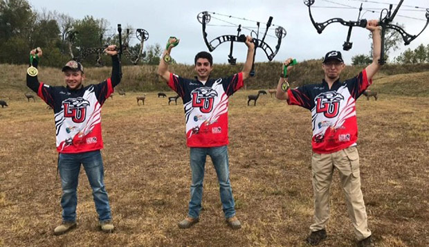 From left, Liberty freshman Louis Boyd, sophomore Spencer Foster, and senior Jason Lynch raise their bows in victory on Sunday in Carrier Mills, Ill. (Submitted photo by Ian Rigney)