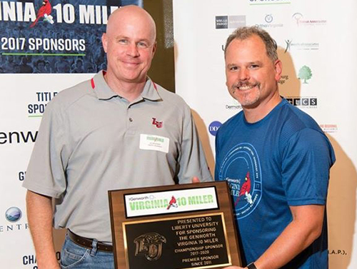 Liberty Senior Vice President of Auxiliary Services Lee Beaumont accepts an award from Jeff Fedorko, Virginia 10 Miler race director, for Liberty's continuous support of the event.