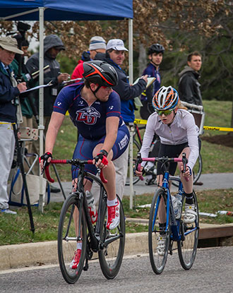 Liberty men's cyclist Brandon Siller escorts in a female rider after a crash.